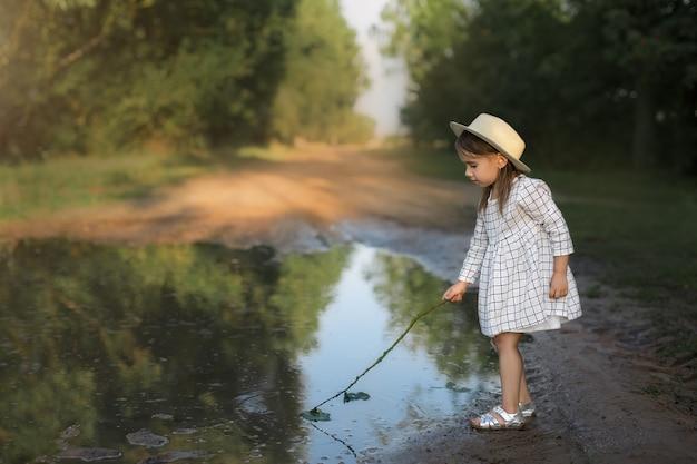 雨が降った後、女の子が大きくて汚れた水たまりで遊んでいます。