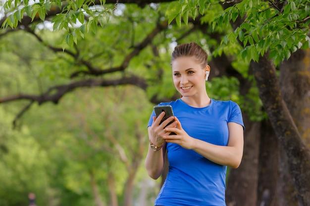 女の子がヘッドフォンで音楽を聴いて公園でスポーツをする