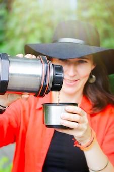 女の子が散歩中に魔法瓶からお茶を注ぐ。森の中を散歩したり、ピクニックに立ち寄ったりする形でのアクティブなレクリエーション。