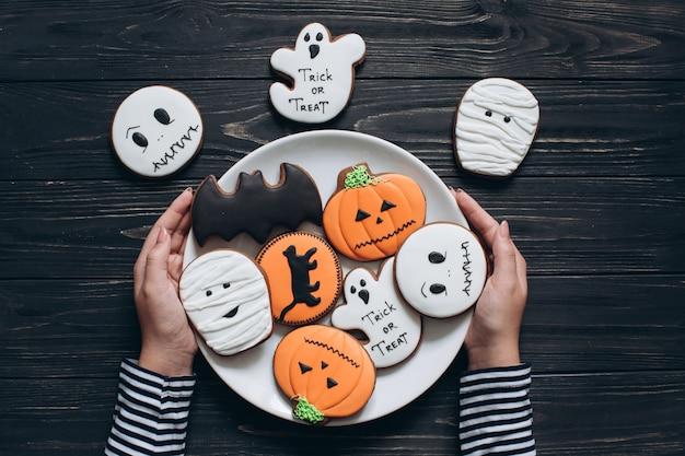 Девушка готовится к хэллоуину и держит тарелку с страшными пряниками.
