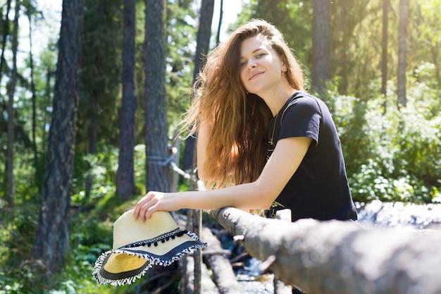 Отдыхающая в походе девушка держит в руках шляпу на фоне густого леса