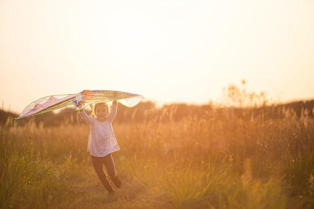 한 소녀가 연을 들고 들판에 뛰어들어 연을 쏘는 법을 배웁니다. 여름의 야외 엔터테인먼트, 자연과 신선한 공기. 어린 시절, 자유와 부주의. 날개를 가진 아이는 꿈이자 희망입니다.