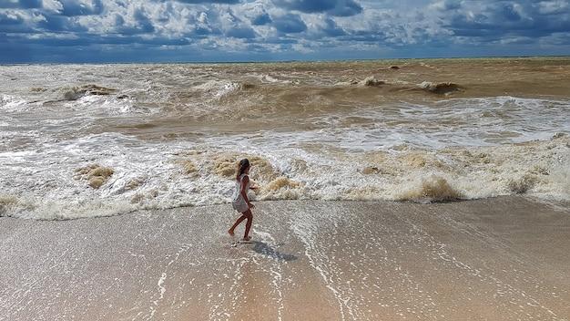 Девушка бежит по песчаному пляжу. огромные пенные волны и тяжелые дождливые облака. буря. черное море