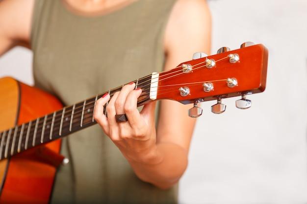 彼女が首にアコースティックギターを持っているときの女の子の手