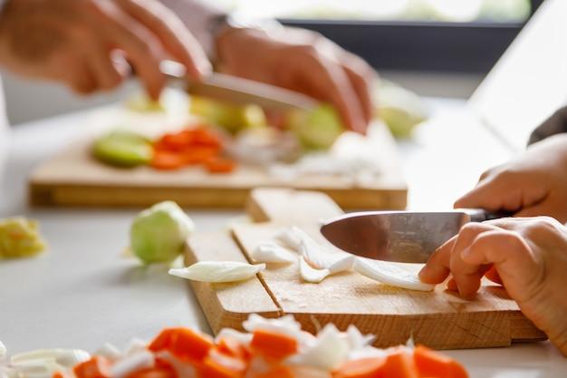 Руки девушки и ее отца режут овощи для приготовления пищи