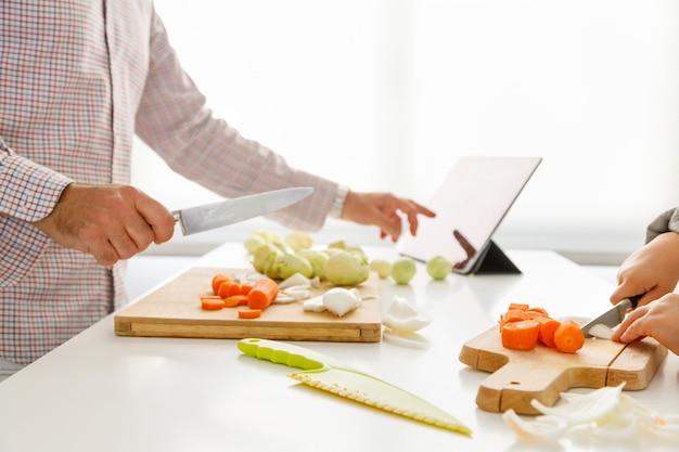 Руки девушки нарезают овощи, чтобы приготовить, а отец смотрит на рецепт на планшете