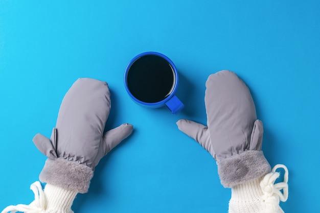 Руки девушки в рукавицах и чашка черного кофе на синем фоне. горячий напиток и варежки.