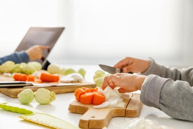 Руки девушки готовят еду на кухне, а ее брат смотрит на планшет