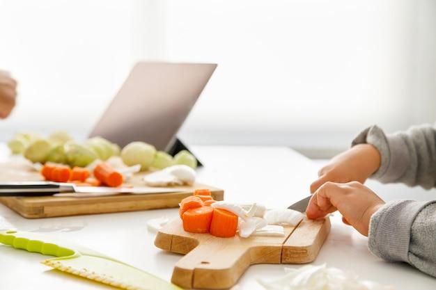 Руки девушки, приготовление пищи на кухне с планшета на заднем плане