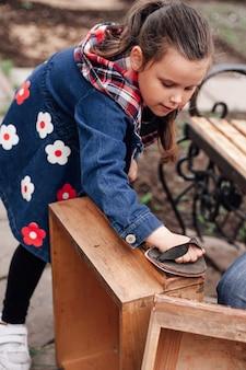 Девушка шлифует старый деревянный ящик шкафа наждачной бумагой - полезное времяпрепровождение и образ жизни