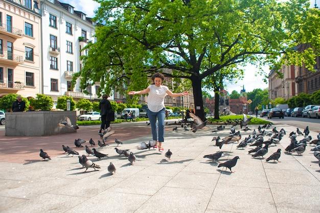 Девушка пугает стаю голубей на городской площади