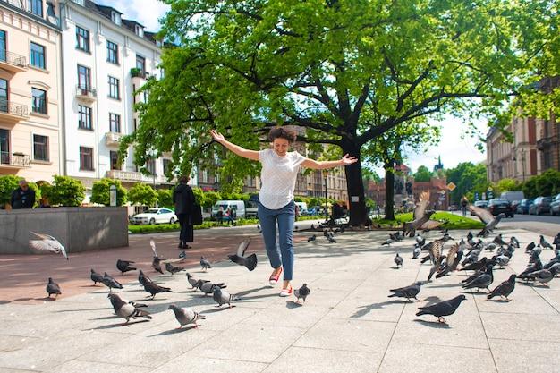 Девушка пугает стаю голубей на городской площади.