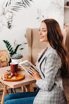 カフェに座ってタブレットを見る女の子、喫茶店の女の子が微笑む、遠い仕事。
