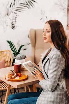 カフェに座ってタブレットを見ている女の子、コーヒーショップの女の子が微笑んでいる、遠い仕事
