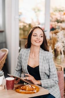 Девушка сидит в кафе и смотрит на планшет, девушка в кафе улыбается, дистанционная работа.