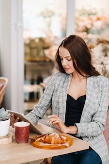 カフェに座ってタブレットを見る女の子、喫茶店の女の子が微笑む、遠方の仕事