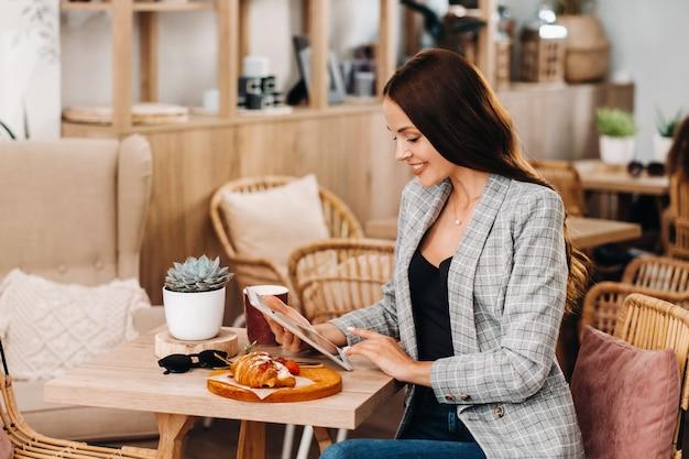 カフェに座ってタブレットを見る女の子、コーヒーショップの女の子が微笑む、