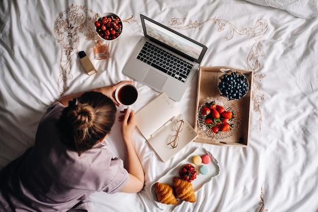 Девушка вечером сидит в постели со смартфоном в руке и ест клубнику, девушка в постели ест сладости перед сном ..