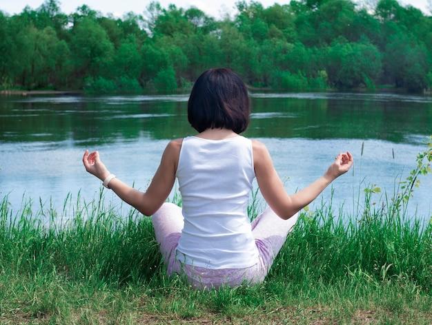 한 소녀가 강가의 풀밭에 등을 대고 명상 포즈를 취하고 있다