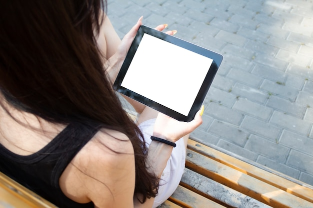 Девушка сидит на скамейке и держит в руках планшет с белым экраном.