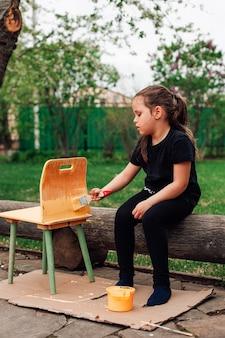 Девушка сидит на бревне в саду и красит устаревшую сломанную мебель в новый цвет семейный бизнес ...