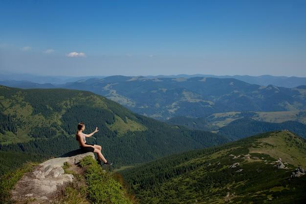 Девушка сидит на краю обрыва и смотрит на солнечную долину и горы.