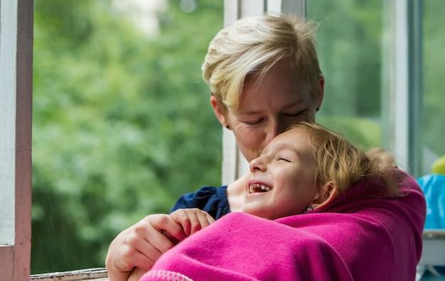 開いた窓の近くに子供と一緒に座っている女の子が、格子縞に包まれた笑っている女の子を抱きしめています。