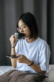 座っていると寝室でコーヒーを飲む女の子。