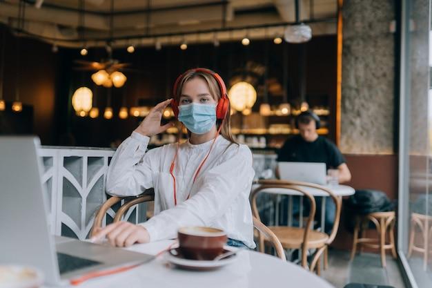 ヘッドフォンコロナウイルスの発生とコーヒーショップに座っている女の子