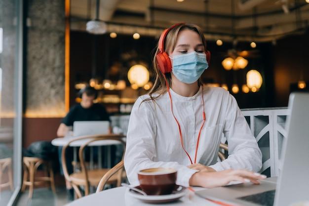 ヘッドフォンでコーヒーショップに座っている女の子コロナウイルスの発生