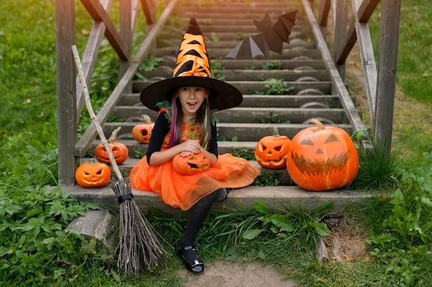 Девушка сидит на лестнице с удивленным лицом на хэллоуин