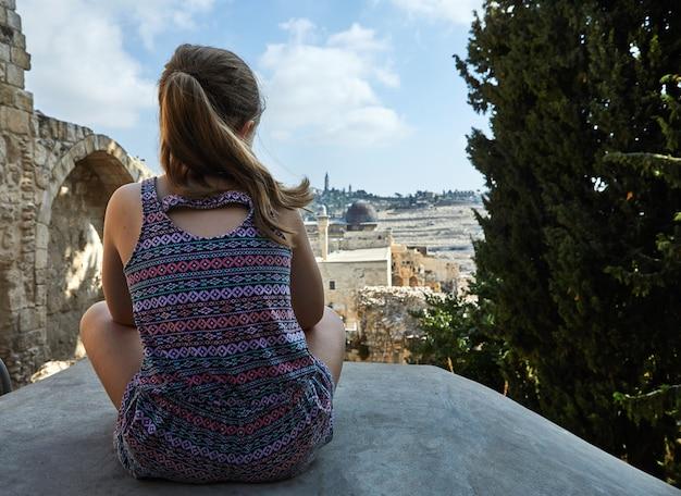 예루살렘의 옛 도시의 돌에 앉아 도시의 파노라마에서 거리를 바라 보는 소녀