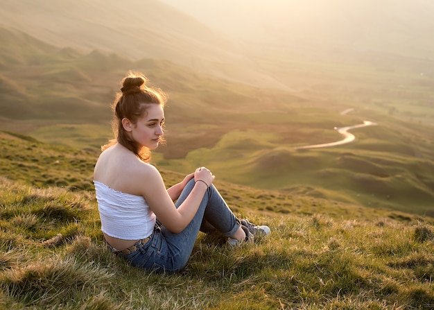 Девушка сидит на вершине холма на фоне удивительного пейзажа на закате летом