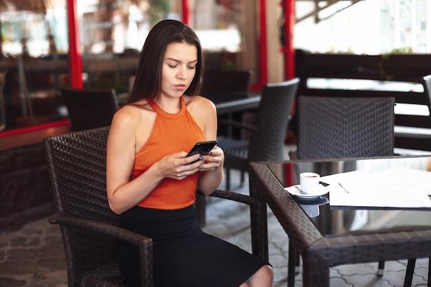 그녀의 손에 전화 앉아 여자는 화면 앞에 그녀의 슬픈 커피 한잔을 찾습니다