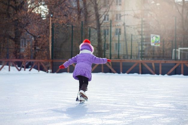 Девушка зимой катается на коньках на катке. каток во дворе города. ребенок учится кататься на коньках