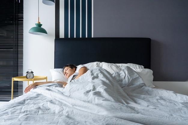 目覚まし時計の横で眠っている少女。起きる時間。目覚まし時計で午前7時深い眠り。