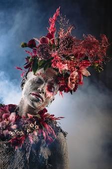 Намазанная глиной девушка в зацементированном платье. у модели головной убор из цветов. дым сзади