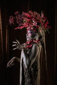 Намазанная глиной девушка в зацементированном платье. у модели головной убор из цветов.