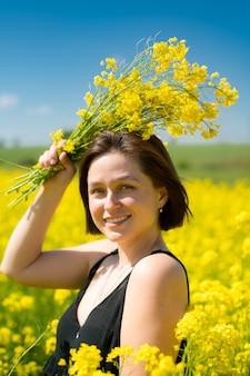 Девушка улыбается в желтом поле летом