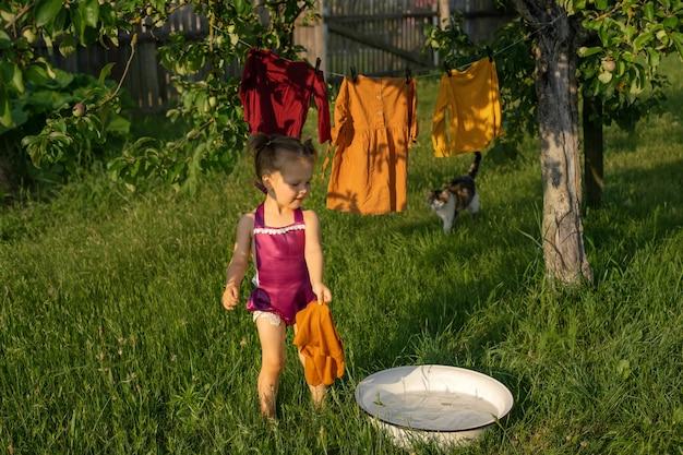 女の子が石鹸水で洗面器に水しぶきをかけ、衣類を洗い、衣類を干して乾かします