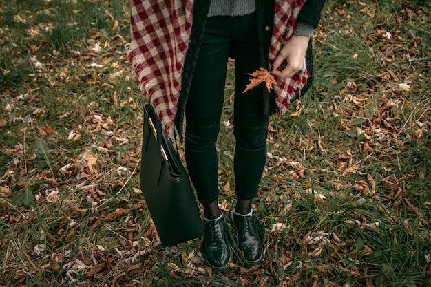 Девушка стоит и держит осенний лист на фоне травы, на которой лежат осенние листья