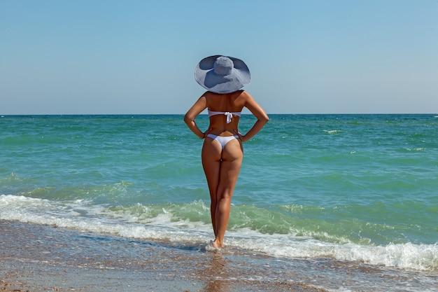 한 소녀가 바다를 마주보고 서 있고, 해안가에 혼자