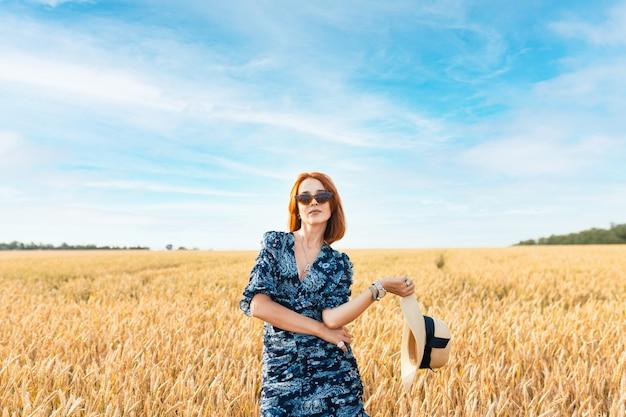 한 소녀가 황금빛 밀밭에 서 있습니다. 해질녘 밀 귀 사이에 낭만적인 모자를 쓴 어린 소녀.