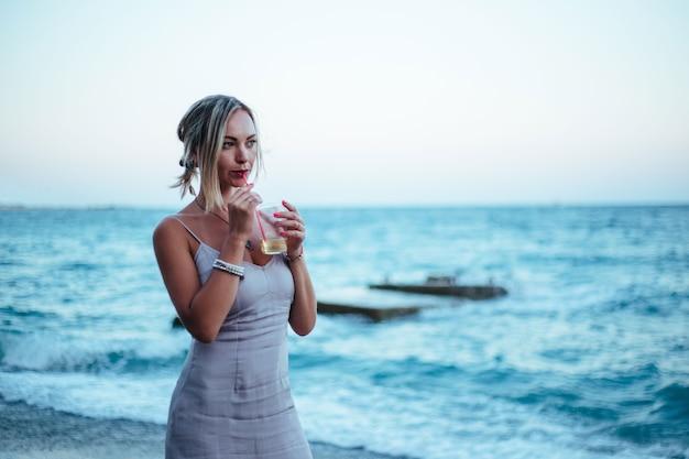 Девушка стоит у моря и пьет коктейль
