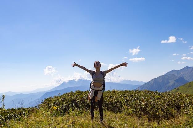 山の頂上に立っている女の子が手を上げる