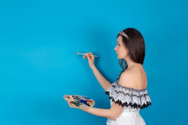 スタジオの青い背景に明るい色で絵筆とパレットを手にした、美術学校の芸術家の職業の女子学生