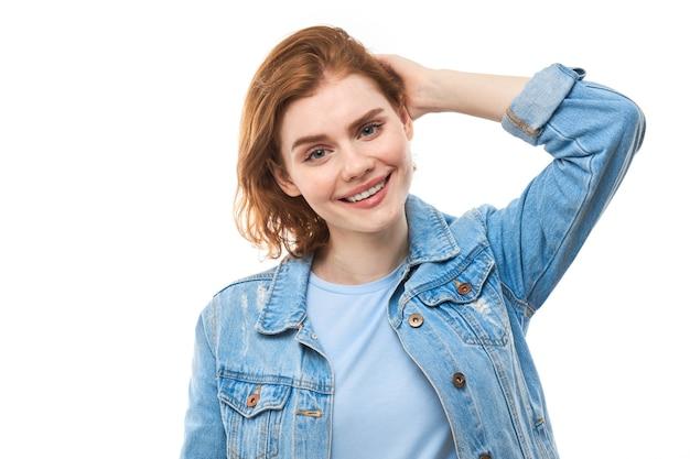 Студентка с рыжими волосами радостно думает и смотрит в камеру, держа палец возле подбородка. задумчивая вдумчивая женщина в синей джинсовой куртке на белом фоне. копировать пространство