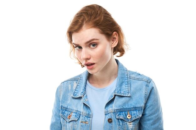 Студентка с рыжими волосами радостно думает и смотрит в камеру, держа палец возле подбородка. задумчивая задумчивая женщина в синей джинсовой куртке на белом фоне. копировать пространство
