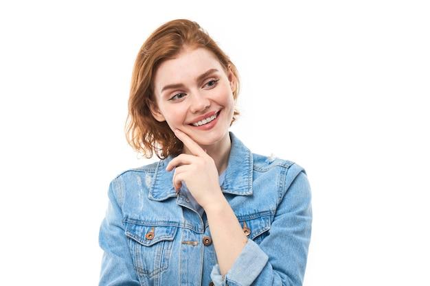 赤い髪の女子小学生は、あごに指を近づけながらカメラを見て喜んで考えます。白い背景の上の青いデニムジャケットで物思いにふける思いやりのある女性。コピースペース