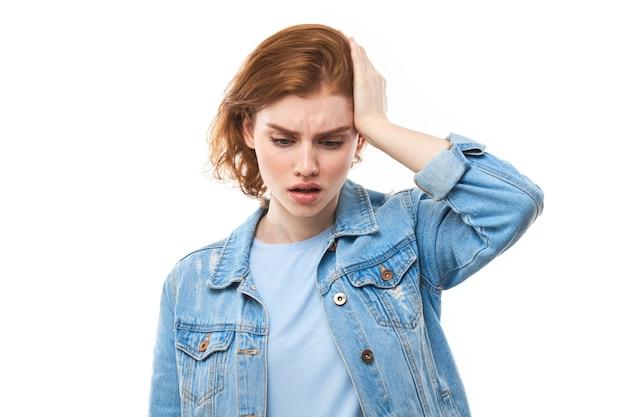 Студентка с рыжими волосами, стоя с открытым ртом, держа руку на голове, забывает что-то важное, женщина стоит на белом изолированном фоне. проблемы с памятью